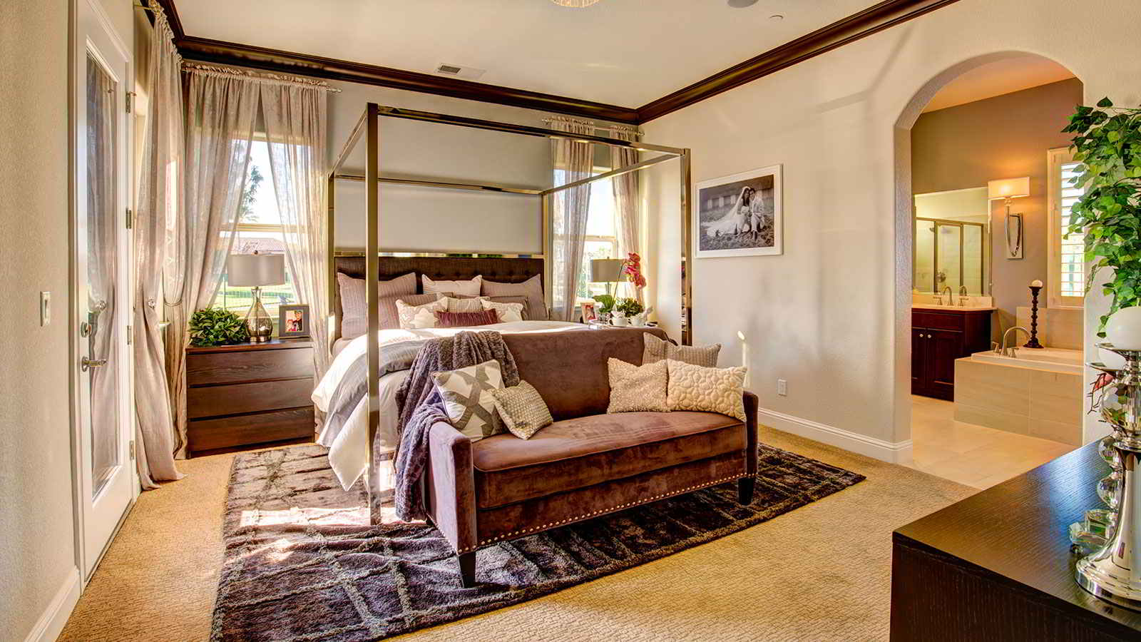 A warm neutral toned room, with a plush bench at the foot of the mid-century modern style bed.