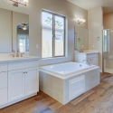 A view of the vanity, his-and-hers sinks, tub, and walk-in shower in the owner bathroom.