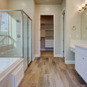 Walk-in shower, tiled-in bathtub, and dual sinks in the owner bathroom, which leads to the master closet.
