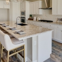 Spacious kitchen island table with four bar stools and place settings.