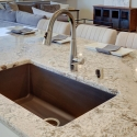Large kitchen island with built-in composite granite sink.