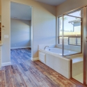 Large tiled in tub and walk-in shower with built-in sitting shelf.