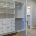Spacious walk-through master closet with built in shelving, drawers, and hanging rods.