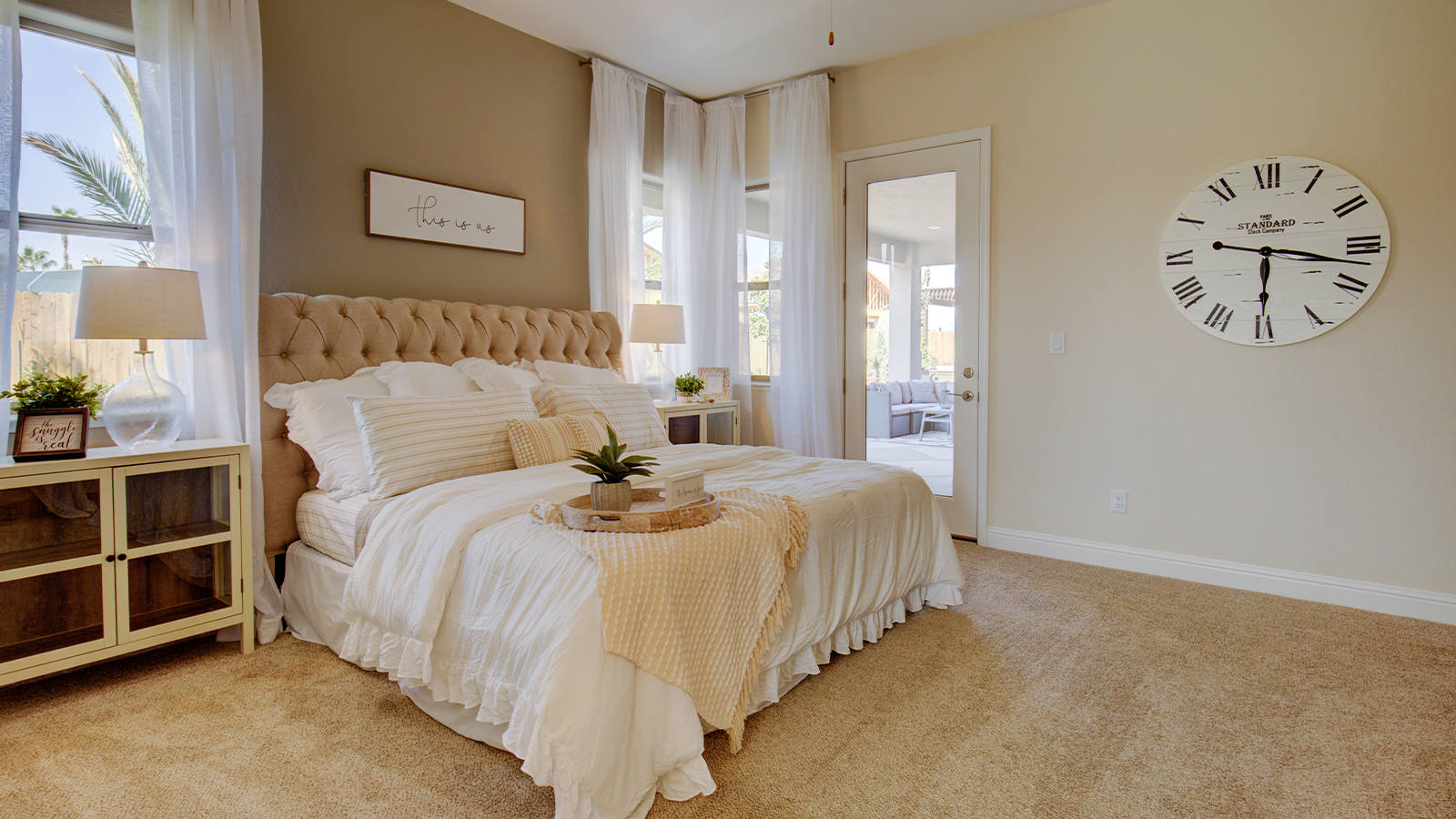 A plush tufted headboard and fluffy white and natural toned bedding create an inviting space to sleep in this Bella owner's suite.