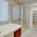 Tiled-in bathtub and step-in shower in the Owner's Bathroom.