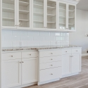 Display and storage cabinets across from the kitchen.