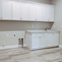 Custom cabinetry and utility sink in the laundry room.