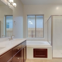 Dual sinks, tiled-in bathtub, and step-in shower in the owner's bath.