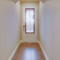 View of the white wrought-iron front entry door from the hallway.