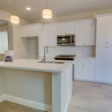 The kitchen, featuring white cabinets and a large kitchen island.