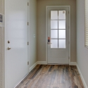 The windowed front entry door, as seen from the hallway.