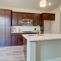 The kitchen, with large kitchen island and dark java cabinets.