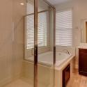 The step-in shower and tiled-in tub in the owner's bathroom.
