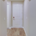 The front entry door as seen from the hallway, with doors to the second bath and third bedroom to the left.