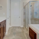 The owners bath with dual sinks to the left, and the bathtub and step-in shower to the right. The doorway to the owner's closet is center.