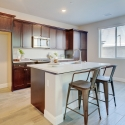 The kitchen, with large kitchen island and dark java finish cabinets.