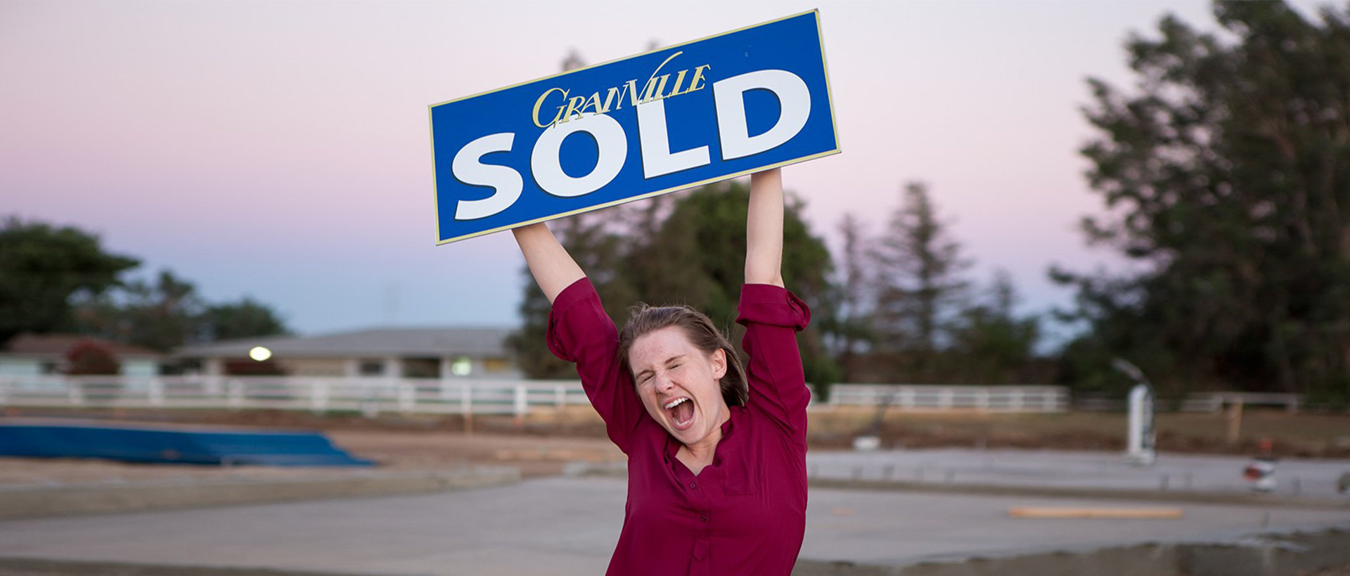 A new homeowner proudly showing off a SOLD sign.