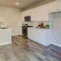 The kitchen, featuring white cabinets and white quartz countertops.
