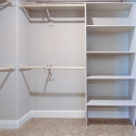 The walk-in owners closet, with hanging rods and shelving.
