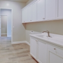 The laundry room, featuring upper and lower cabinets and utility sink.