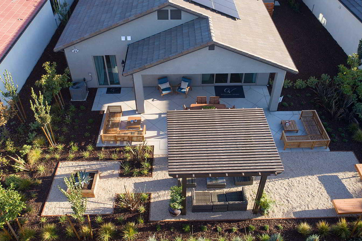Aerial shot of drought-tolerant backyard and patio landscaping with a pergola.