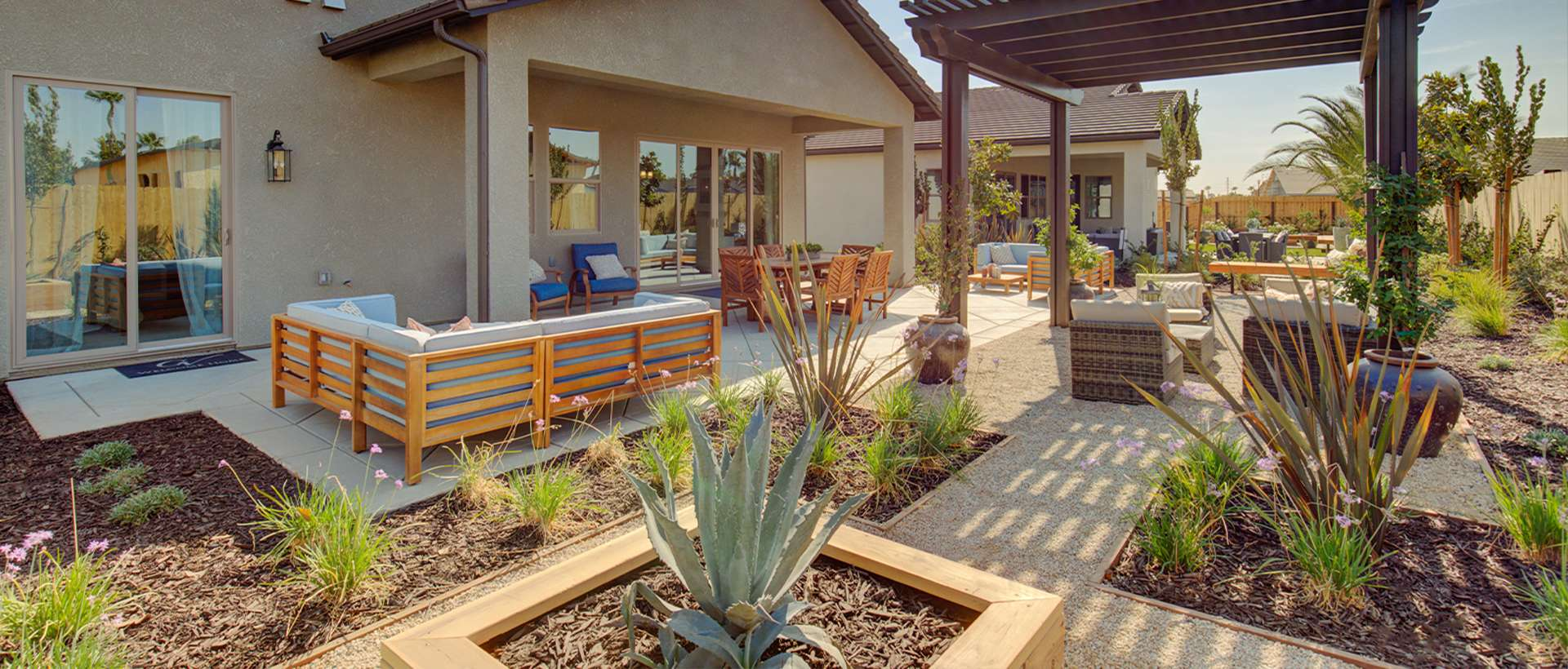 Drought tolerant backyard and patio landscaping with a pergola.