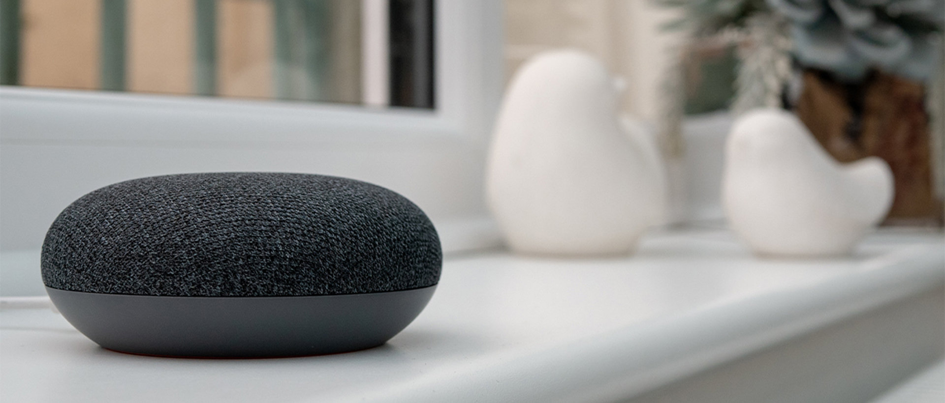 A Google Nest Mini sitting on a windowsill.
