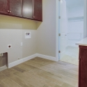 The laundry room, with upper and lower dark java cabinets.