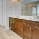 Dual sinks and dark java cabinets with white quartz cabinets in the owner's bath.