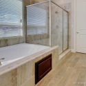 The tiled-in bathtub and walk-in tiled shower in the owner's bath.