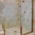The shower featuring stone tiles and a built-in shelf or sitting ledge.