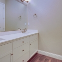 Dual sinks, white quartz countertops, and white cabinets in the second bathroom.