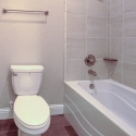 The toilet and tile-wall bathtub in the second bath.