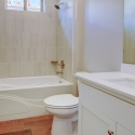 The third bath, with tile wall tub, white quartz countertop, and white cabinet.