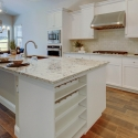 The kitchen, featuring bright granite slab countertops, large kitchen island with built in wine rack, and white cabinets.