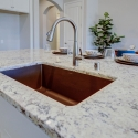The gray granite composite kitchen sink, located at the kitchen island. You can see the details of the granite slab countertop.