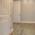The laundry room, featuring large double-door closet, as well as white upper and lower cabinets.