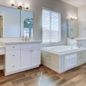 The owner's bath, featuring dual sinks, vanity, large soaking tub, and tile walk-in shower.