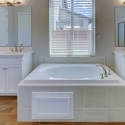 The dual sinks frame either side of the large tiled-in soaking tub.