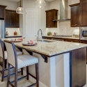The kitchen, with granite slab countertops and dark java cabinets,