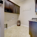 The laundry room, with upper and lower cabinets, and utility sink.