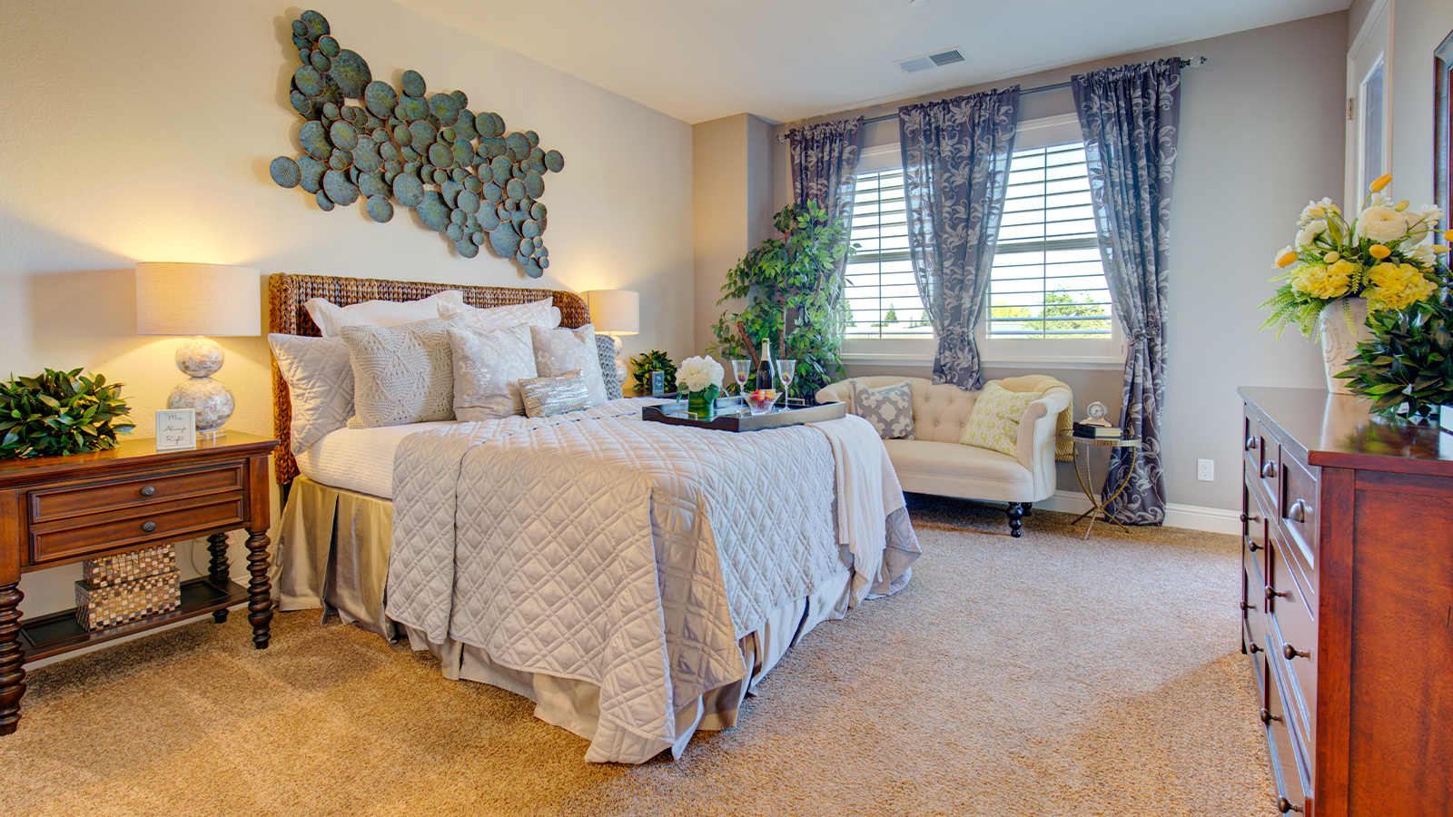 An owner's suite, shown staged with greenery and cool blue and green decor. There are wide fauxwood blinds on the window and lush printed curtains.