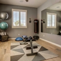 The fourth bedroom, located downstairs, shown staged as a home gym.