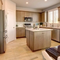 The kitchen, with large kitchen island and light wood cabinets.