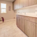 The laundry room, with upper and lower cabinets and utility sink.