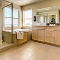 The owner's bath, with dual sinks and natural wood cabinets.