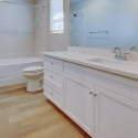 The second bathroom, with tile wall bath and white quartz countertop.