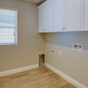 The laundry room, with white upper cabinets.