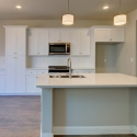 The kitchen and dining nook, featuring large kitchen island and hanging lights.