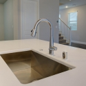 The stainless steel sink, located at the kitchen island.